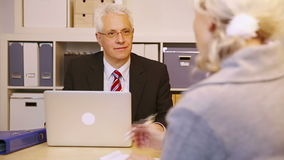 Consultant talking to elderly customer in office stock video footage