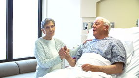 Consultant Talking To Senior Couple In Hospital Room stock video footage