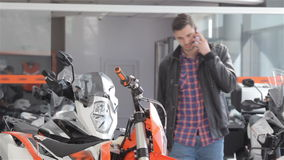 Consultant talks on the phone at motorbike salon. Brunette man talking on the phone at motorcycle dealership. Caucasian guy coming up to the one of motorcycles stock video