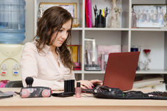 Consultant working in the cosmetics laptop. Young woman sitting at office table, laid out on the table cosmetics Stock Photos