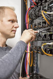 IT consultant working with network switches. IT engineer or technician working with network cabling and installation of communication switches in datacenter royalty free stock image