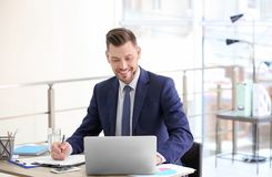 Consultant working at table. In office stock photo