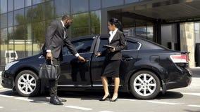 Consultante da sala de exposições do carro que mostra o carro luxuoso ao comprador, negócio de aluguel do veículo imagem de stock