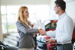 Consultante fêmea novo das vendas do carro que trabalha na sala de exposições foto de stock