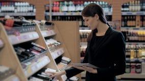 Consultante na loja de vinho, oman na loja que escolhe o vinho que concorda a lista ou a informação de verificação no tablet pc video estoque