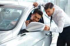 Consultante Showing das vendas do carro um carro novo a um comprador potencial em S fotografia de stock royalty free