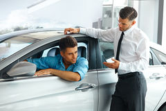 Consultante Showing das vendas do carro um carro novo a um comprador potencial em S foto de stock royalty free