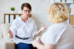Consultation. Confident specialist consulting her patient Royalty Free Stock Photo