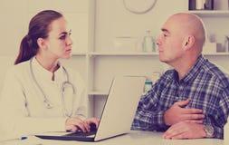 Consultation de visite de client d'homme avec le docteur féminin photos libres de droits