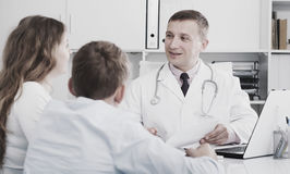 Consultation with doctor. Middle-aged mother and son visiting consultation with men doctor in hospital Royalty Free Stock Photos