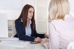 Consultation at office with young woman and female consultant. Royalty Free Stock Photo