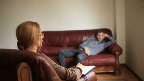 Consultation of a psychologist, a female therapist is consulting a patient with a man with an anxiety disorder stock video footage