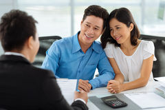 Consultation with real estate agent. Middle-aged Vietnamese family having consultation with real estate agent Royalty Free Stock Images