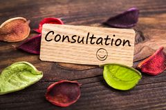 Consultation word in card. Consultation word in wooden card with dried flower on wood royalty free stock photo