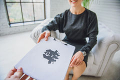 Consulter showing paper with inkblot Royalty Free Stock Photos