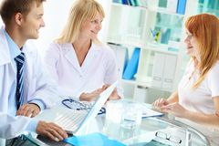 Consulting. Portrait of confident practitioners consulting patient in hospital Stock Photo