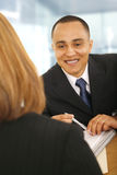 Consulting. Business man smiling while talking to business woman. concept for business deal, meeting, sales, or consulting Royalty Free Stock Photography