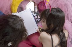 Consulting the agenda. Two little girls looking in an agenda Royalty Free Stock Image