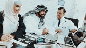 男性医生Consulting在医院的Arabic Family 库存照片