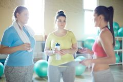 Consulting at break. Two plus-sized women listening to their instructor announcing results of the last training at break royalty free stock image