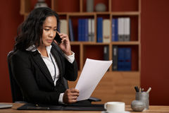 Consulting client. Female Asian lawyer reading contract and consulting client on the phone Royalty Free Stock Image