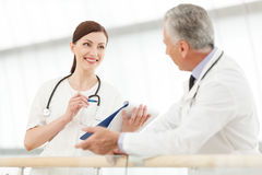 Consulting with colleague. Female doctor communicating with her Royalty Free Stock Photo