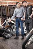 Consulting customer. Young cheerful young sales executive consul. Ting customer about motorcycle Royalty Free Stock Images