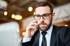 Consulting about data. Serious agent or broker speaking by mobile phone and consulting his client stock photography
