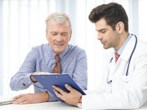 Consulting with doctor. Young male doctor holding flip chart in his hands and consulting with old patient at hospital Stock Photos