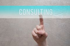 Consulting  - finger pressing blue button. Consulting  - finger pressing blue  virtual transparent button on grunge light brown background with copy space for Stock Images