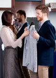 Consulting with girlfriend while selecting a shirt Royalty Free Stock Photos