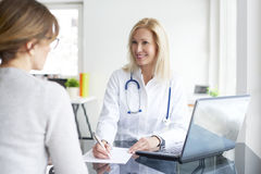 Consulting in the hospital. Shot of a middle aged female doctor sitting at desk in front of laptop and consulting with her patient Royalty Free Stock Photography