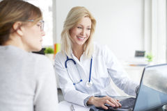 Consulting in the hospital. Shot of a middle aged female doctor sitting at desk in front of laptop and consulting with her patient Royalty Free Stock Photo