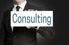 Consulting sign is held by businessman Stock Images