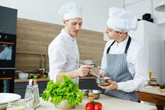 Consulting trainee. Chef with whisk mixing raw eggs in steel bowl while consulting his trainee in the kitchen Royalty Free Stock Photos