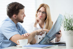 Consulting the xray. Young pretty doctor consulting with colleague patient's xray photo Royalty Free Stock Photo