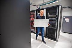 Consultor Carrying Blade Server de las TIC mientras que camina en Datacenter Foto de archivo libre de regalías