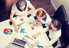 Consultor de inversión de la mujer de negocios tres que analiza informe financiero anual de la compañía Foto de archivo
