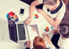 Consultor de inversión de la mujer de negocios tres que analiza informe financiero anual de la compañía Fotografía de archivo