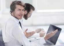 Consultor en los auriculares que se sientan en su escritorio imagenes de archivo