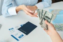 Consultor femenino joven del agente de viajes en agencia del viaje con un primer del pago al contado del cliente fotos de archivo libres de regalías