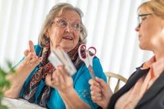 Consultor financiero Handing Scissors a señora mayor Holding Credit Cards imagen de archivo libre de regalías