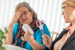 Consultor financiero Hands Scissors a la señora mayor con las tarjetas de crédito foto de archivo