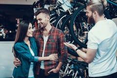 Consultor Helps Young Couple en elegir de la bici imágenes de archivo libres de regalías