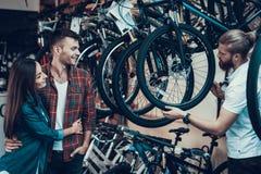 Consultor Helps Young Couple en elegir de la bici fotografía de archivo libre de regalías