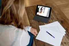 Consultor independiente hermoso de la mujer que tiene una llamada de la videoconferencia con el cliente en línea en casa fotografía de archivo
