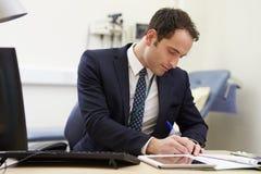 Consultor masculino Working At Desk en oficina fotografía de archivo libre de regalías
