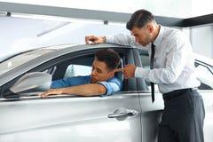 Consultor Showing de las ventas del coche un nuevo coche a un comprador potencial Imágenes de archivo libres de regalías