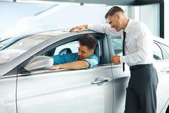 Consultor Showing de las ventas del coche un nuevo coche a un comprador potencial en S Foto de archivo libre de regalías