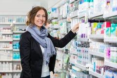 Consumatore femminile sorridente che sceglie prodotto dentro fotografia stock libera da diritti